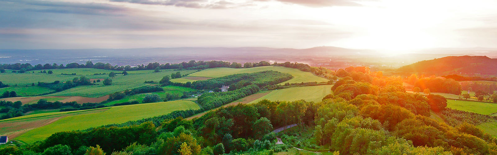 Sunset, with lens flare, in summer looking towards the Royal Forest of Dean from Painswick Beacon