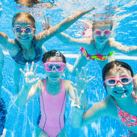 Friends enjoying themselves in a swimming pool on a sunny day.