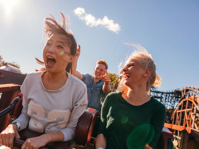 3 friends having fun on a roller coaster.
