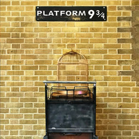 Sign with Platform 9 3/4 on it, above a trolley with suitcases.