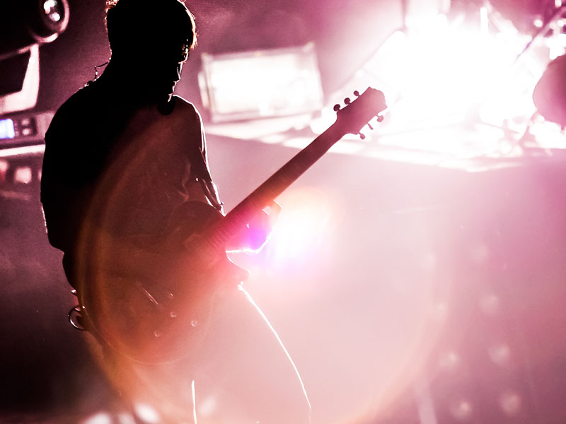 A man playing the guitar at a music venue.