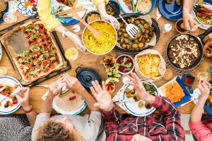 A table full of food with people enjoying a meal.