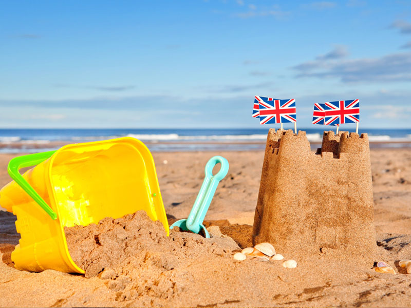 British Seaside traditional sand castle on the beach with bucket and spade shells and Union Jack Flags.