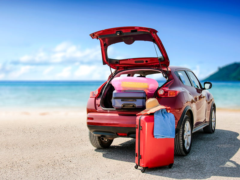 Summer time and red car on beach with few suitcase.