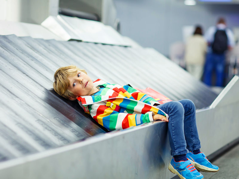 Child waiting with kids suitcase on baggage carousel.