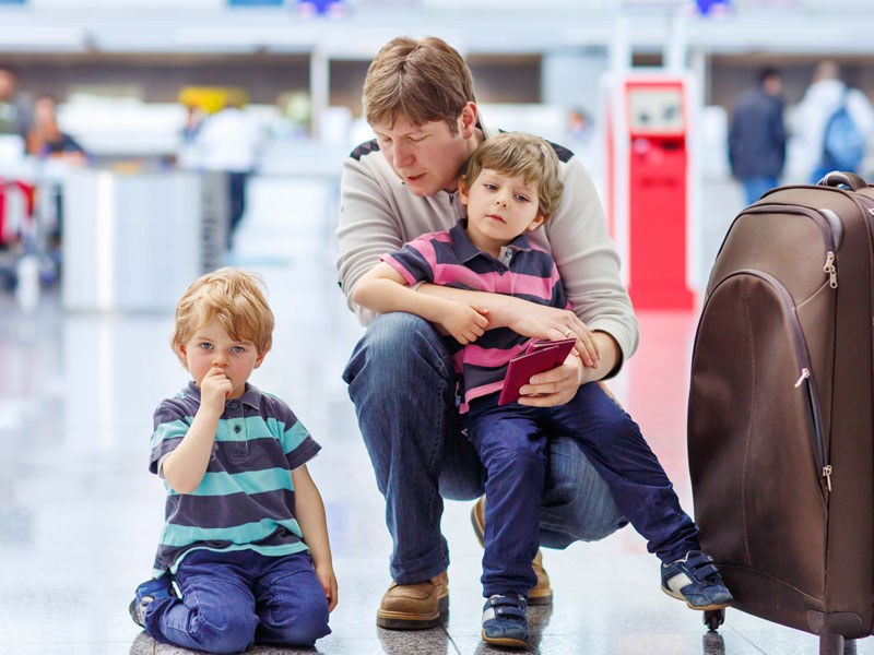Tired father and two little sibling kids boys at the airport,